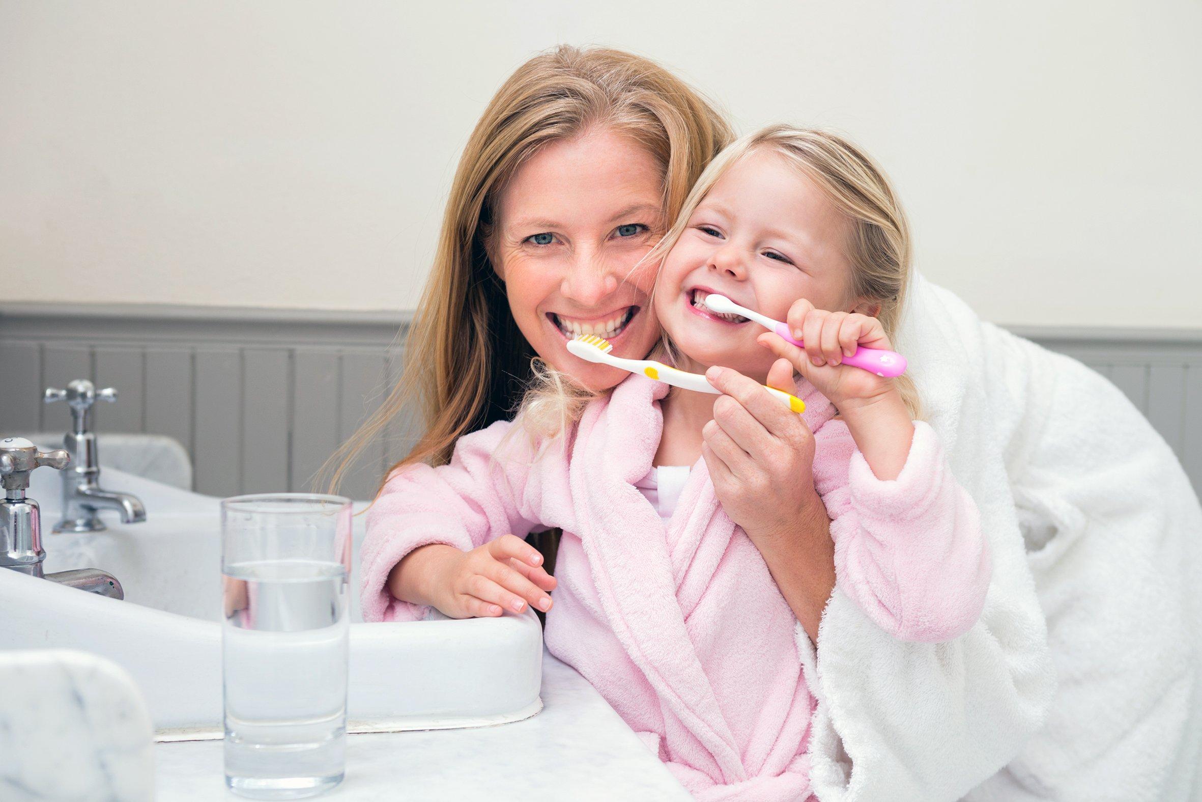 madre e hija cepillándose los dientes - unidad de periodoncia Las Palmas