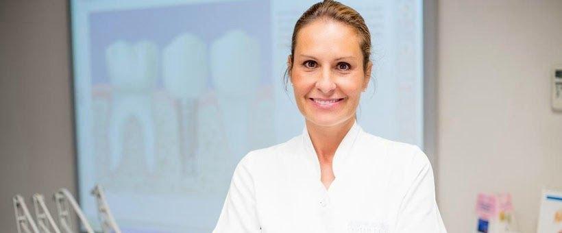 Dra. Adalia con una imagen de implantes dentales en la Clínica Dental Adalia